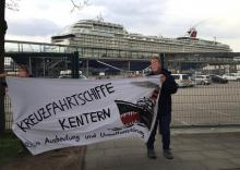 """""""Mein Schiff 1"""" hinter Transparent gegen Kreuzfahrtschiffe in Kiel"""