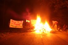 "Solidarity photo for Rojava. A burning barricade, a banner wich says ""From Hambi to Rojava your struggle is ours!"" and a YPJ flag"