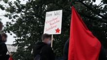 Schild mit Text: Unsere Wahl: Klassenkampf, Revolution, Sozialismus!